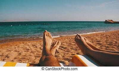 Legs of Couple People Lying on Beach Sun Lounger near the...