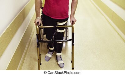 Legs of disabled man in orthosis walking with a walking frame