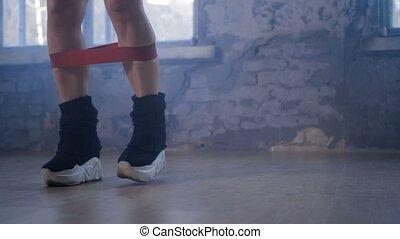 Legs of female exercising elastic resistant band - Close-up...