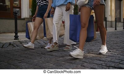 Legs of female friends walking with shopping bags