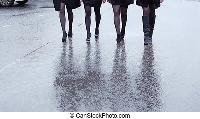 Legs of four woman in shoe on heels walk in lockstep on wet asphalt. Slow motion