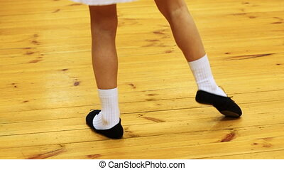 legs of girl does ballet movements while standing on parquet