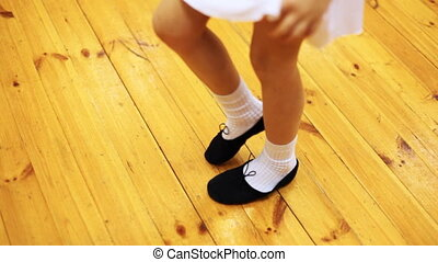 legs of girl doing ballet workout in movement while standing on parquet