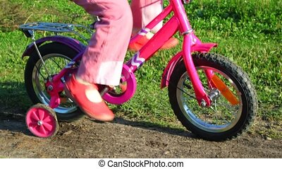 legs of girl pedaling stopped bicycle - legs of little girl...