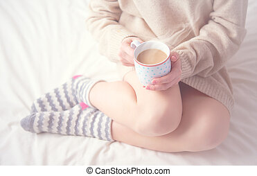 legs of girl warm woolen socks and cup of coffee warming,...