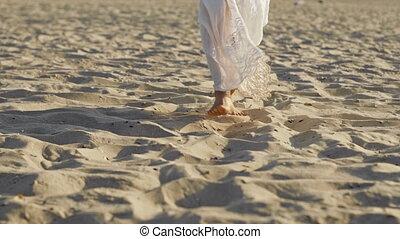 Legs of girl wearing white long dress walking barefoot sand on sea beach or desert. Slow motion. Woman walks to camera. High quality 4k footage