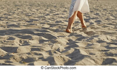 Legs of girl wearing white long dress walking barefoot sand on sea beach or desert. Slow motion. Woman walks away camera. High quality 4k footage