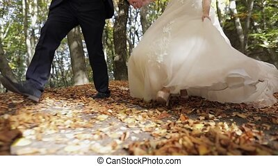 Legs of groom with bride in the forest park. Wedding couple. Happy family