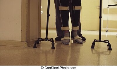 Legs of invalid in orthosis walking with support of two...