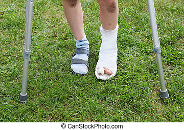 Legs of little boy on crutches; left leg in cast; boy stands...