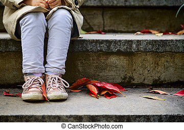 Legs of little girl in stylosh shoes which sitting on the stair in patk with red fallen leaves