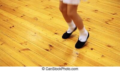 legs of little girl jump doing ballet movements on parquet