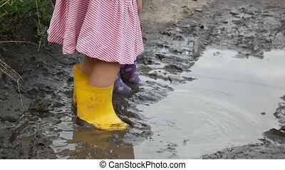 Legs of little girls in rubber boots in a puddle.