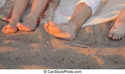 Legs of lovers in the sand on the beach