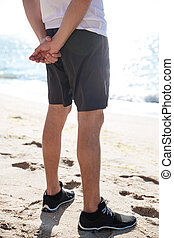 Legs of man in shorts and sneakers standing on beach -...