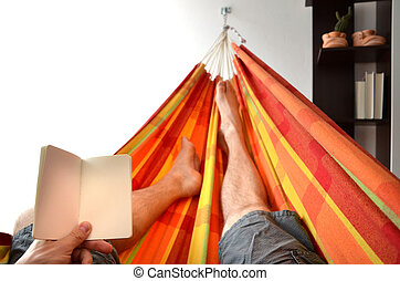 Legs of man lying down in bright hammock holding empty notice book in his hand