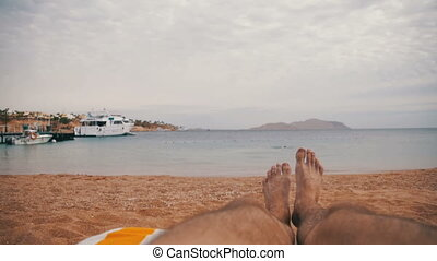 Legs of Man Lying on Beach Sun Lounger near the Sea