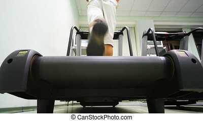 legs of man quickly run on treadmill in empty gym