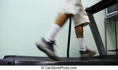 legs of man run on treadmill near wall in gym