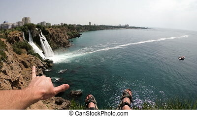 Legs of Man Sitting on the Cliff and Enjoy View of the Picturesque Lower Duden Waterfall Falling into the Sea in Antalya, Turkey. POV.