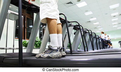 legs of man stand at treadmill in gym, he turn on and begins run