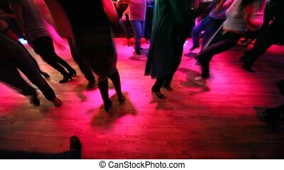 Legs of many dancing men and women in some nightclub with different colors blinking