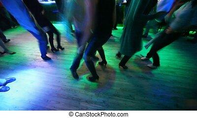 Legs of many dancing men and women in nightclub