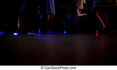 Legs of many men and women on dance floor at night club