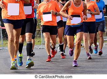 legs of many runners on the road