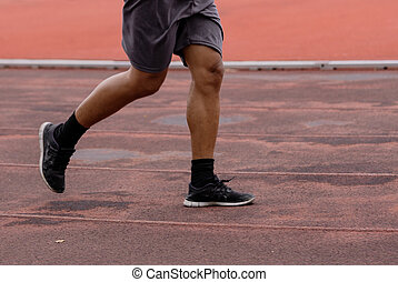 Legs of men jogging in a running track for good health