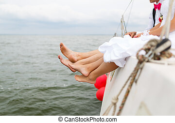 Legs of newlyweds on a yacht at the summer time