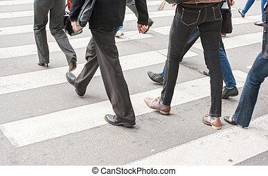 legs of pedestrians in a crosswalk on summer day