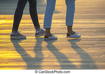 legs of people walking at sunset. Leisure and recreation in the city