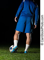 Legs Of Player With Ball On Dark Background