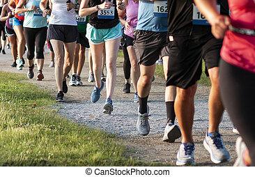 Legs of runners on a dirt path running a 5K race