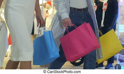 Legs of shopaholics with shopping bags walking down mall....