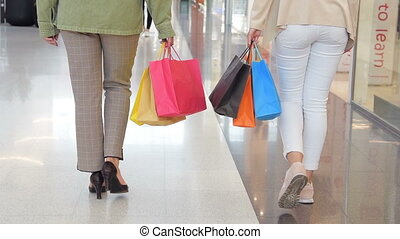 Legs of shopaholics with shopping bags walking down mall. slow-motion. Female women walking at shopping mall.
