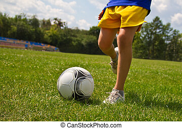 Legs of soccer player kicking the ball