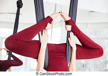Legs of sportswoman doing aerial yoga exercise