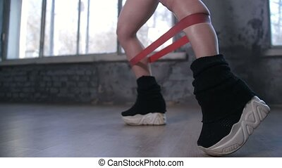 Legs of sporty woman exercising with elastic band - Side...