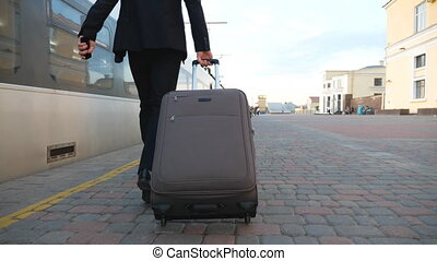 Legs of successful businessman in suit walking along platform and pulling suitcase on wheels. Young confident man with his luggage strolling near train. Concept of business trip. Slow mo Back view