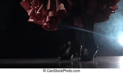 Legs of the girl are tap dancing. Light from behind. Smoke...