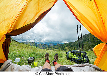 legs of the traveler in hiking boots in a tent outdoors