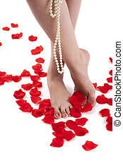 legs of the young girl with rose petals
