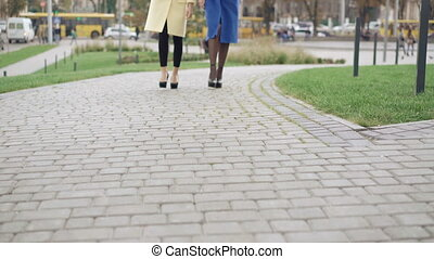 Legs of two girls in coats walking on the pavement 4K