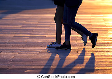 legs of two people walking on the background of sunlight