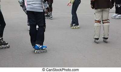 legs of unidentified kids in roller skates on asphalt