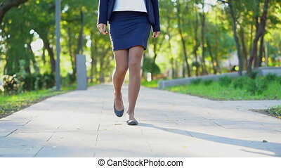 Legs of unrecognizable young business woman in formal wear walking in the green park alone. Girl keeps way to work or university.