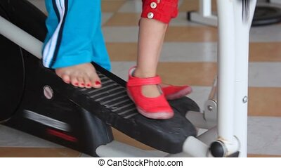 legs of woman and little girl training on gym apparatus