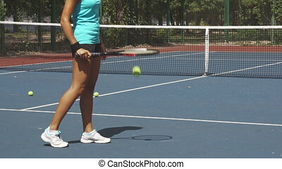 Legs of woman beating tennis racket on ball near net on court